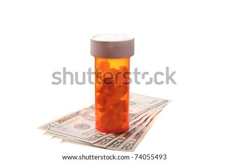 bottle of pills sitting on money - stock photo