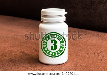 Bottle of pills with Omega-3 on brown background - stock photo
