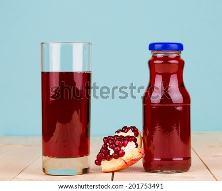 Bottle of pomegranate juice with pomegranates closeup - stock photo