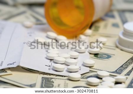 Bottle of prescription pills over dollar bills.  - stock photo