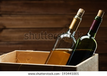 Bottle of red and white wine in wooden box - stock photo