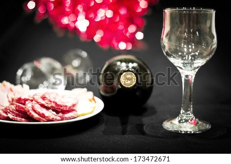 Bottle of red dry wine with wineglasses on a celebratory table. Colorful bokeh background. Image with dark vignette effect - stock photo