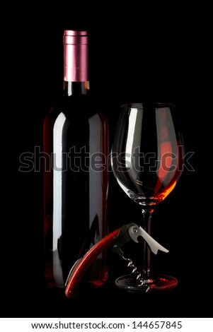 Bottle of red wine, a corkscrew and a wine glass isolated on black background - stock photo