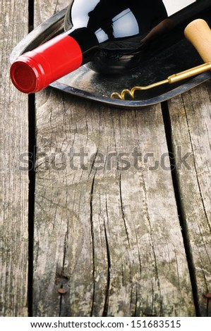 Bottle of red wine and corkscrew on vintage silver tray  - stock photo