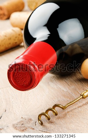 Bottle of red wine and corkscrew on wooden table - stock photo