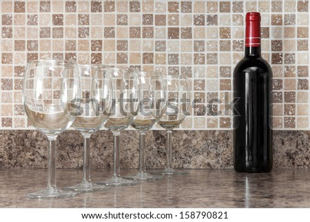 Bottle of red wine and empty glasses on kitchen countertop. - stock photo