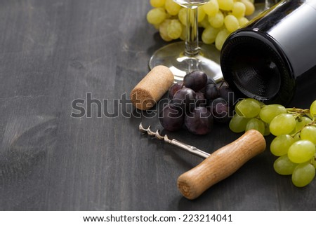 bottle of red wine and grapes on a wooden background, horizontal - stock photo