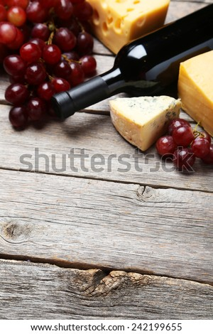 Bottle of red wine, cheeses and grapes on grey wooden background