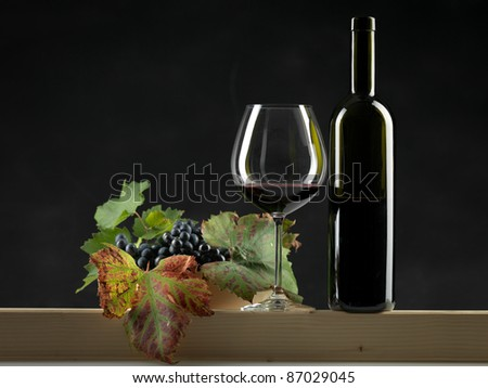 bottle of red wine, glass and bowl of grapes on black background - stock photo