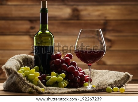Bottle of red wine, glass and grape on a sack in wooden interior  - stock photo