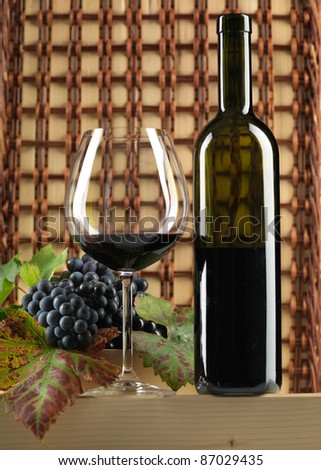 bottle of red wine, glass, grapes on wicker background