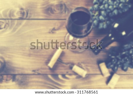 Bottle of red wine, grape and corks on wooden table. Defocused, effect of opaque glass