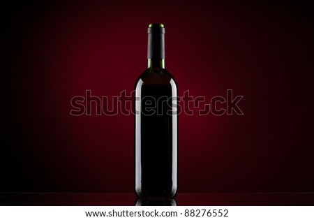 Bottle of red wine on red gradient background - stock photo