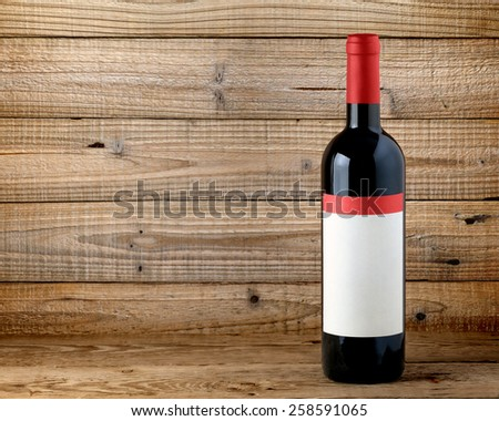Bottle of red wine on wooden background - stock photo