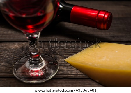 Bottle of red wine with a glass of red wine and a piece of parmesan on an old wooden table. Close up view, focus on the piece of parmesan - stock photo