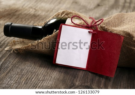 Bottle of red wine with a message on wooden table - stock photo
