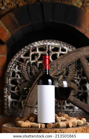 Bottle of red wine with blank label template and glass standing on an old wooden stool with used corks near the fireplace - stock photo