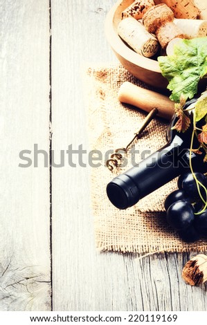 Bottle of red wine with fresh grape and bunch of corks - stock photo