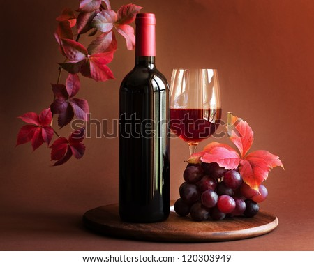 Bottle of red wine with glass, grapes and autumn leaves - stock photo