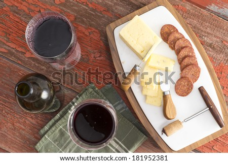 Bottle of red wine with two full glasses served with sliced harvati cheese and spicy sausage as a tasty appetizer to dinner on a rustic wooden table, overhead view - stock photo
