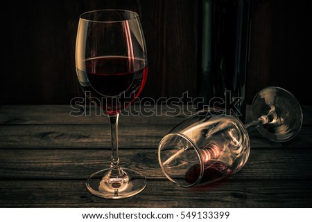 Bottle of red wine with two glasses on an old wooden table. Focus on an overturned glass of wine, image vignetting and the orange-blue toning