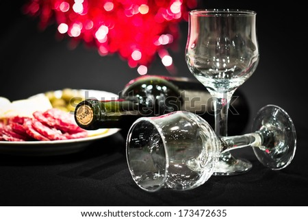 Bottle of red wine with wineglasses on a celebratory table. Colorful bokeh background. Image with dark vignette effect - stock photo