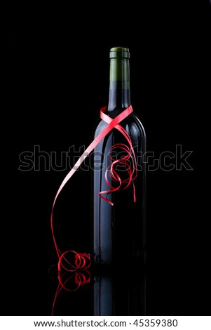 Bottle of red wine wrapped in a red ribbon, Valentines day gift - stock photo