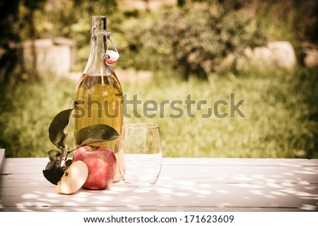 Bottle of refreshing apple juice squeezed from fresh apples harvested in the garden standing outdoors on a rustic wooden table - stock photo