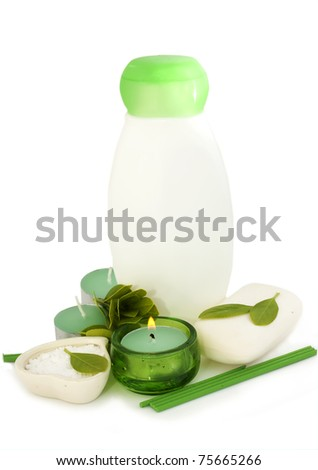 bottle of shampoo,green leaves and candle