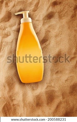 Bottle of sunbath oil or sunscreen on hot beach sand in summer, top view - stock photo