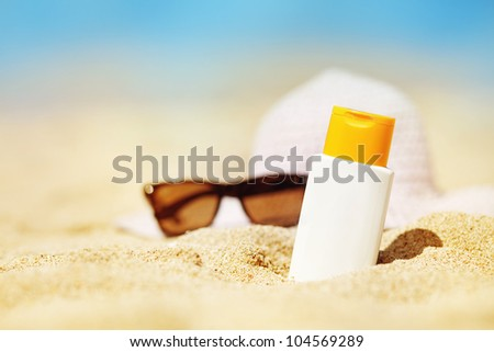 Bottle of sunscreen lotion on the sandy beach - stock photo