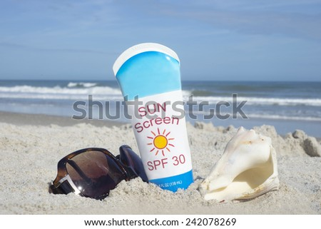 Bottle of sunscreen with shell and sunglasses on beach. - stock photo