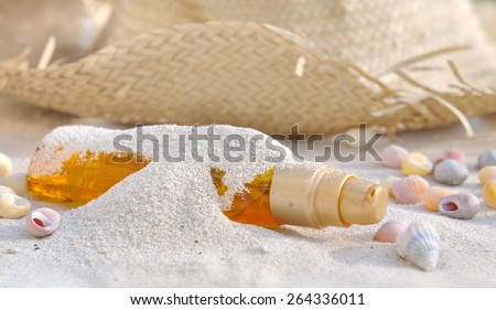 bottle of suntan oil covered by sand with shells and cap - stock photo