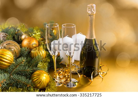 Bottle of unlabelled sealed Christmas champagne to celebrate the season standing with two stylish flutes alongside a pine branch decorated with gold baubles with a blur background with copyspace - stock photo