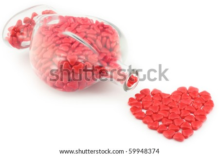 Bottle of Valentine's candies spilled in to a heart shaped design. - stock photo