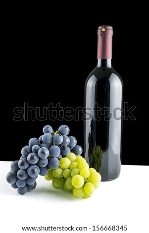 Bottle of vine and grapes on white desk. Isolated over black background.