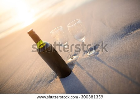 bottle of vine with two glass on the beach - stock photo