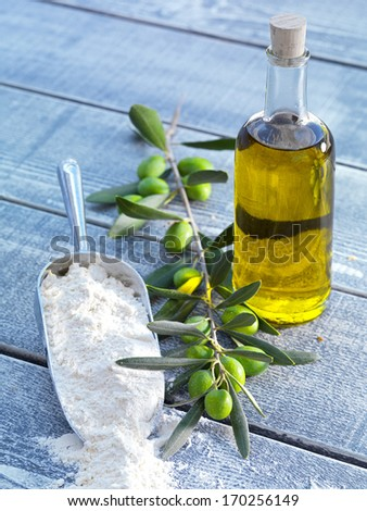 bottle of virgin olive oil,olive branch with ripe green olives and a scoop of wheat flour  - stock photo