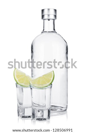 Bottle of vodka and shot glasses with lime slice. Isolated on white background - stock photo