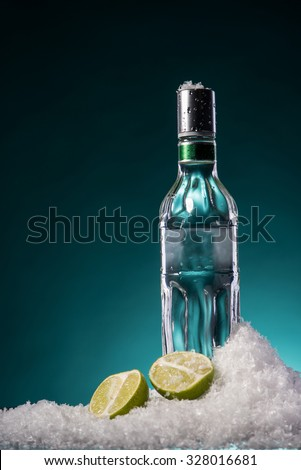 Bottle of vodka and two lime halves with water droplets on a surface in cold ice on green gradient background. Focus on a bottle. - stock photo