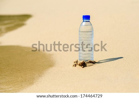 Bottle of water in the sand on the beach - stock photo