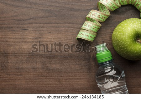 bottle of water, measuring tape and fresh green apple on the wooden table - stock photo
