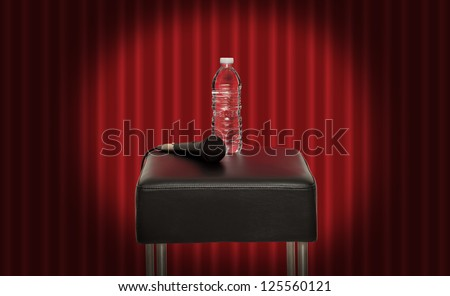 Bottle of water next to a microphone on a stool in the stage - stock photo