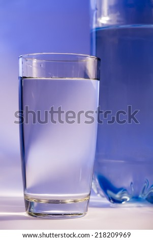 Bottle of water with glass - stock photo