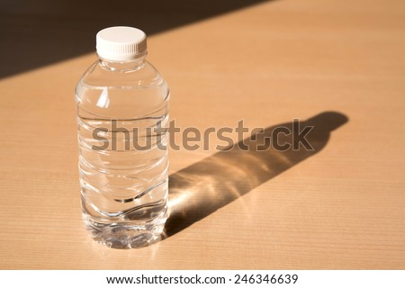 Bottle of water  with light and shadow on wooden table - stock photo