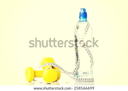 Bottle of water with measuring tape and weights.  - stock photo