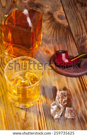 Bottle of whiskey and a glass and tobacco pipe on a wooden table