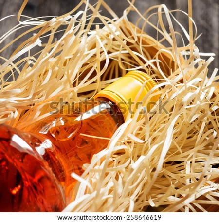 Bottle of whiskey in a wooden box on a black wooden table in background. Scotch and Irish Single Malt or Blended Whiskey is classic drinks for real men. Close-up view. - stock photo