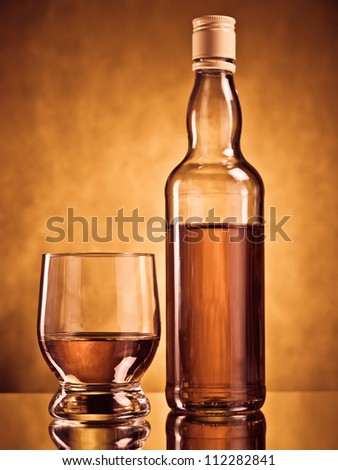 Bottle of whiskey with a filled glass - stock photo