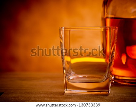 Bottle of whiskey with an empty glass waiting to be filled - stock photo